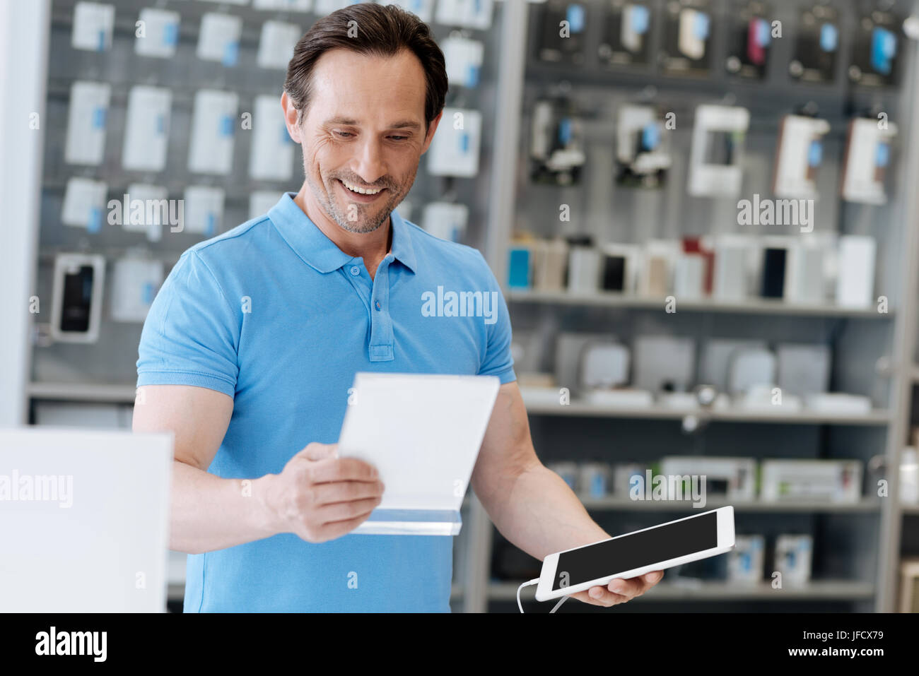 This model is perfect for me. Adult man wearing a bright blue polo smiling to himself while choosing a new gadget - Stock Image