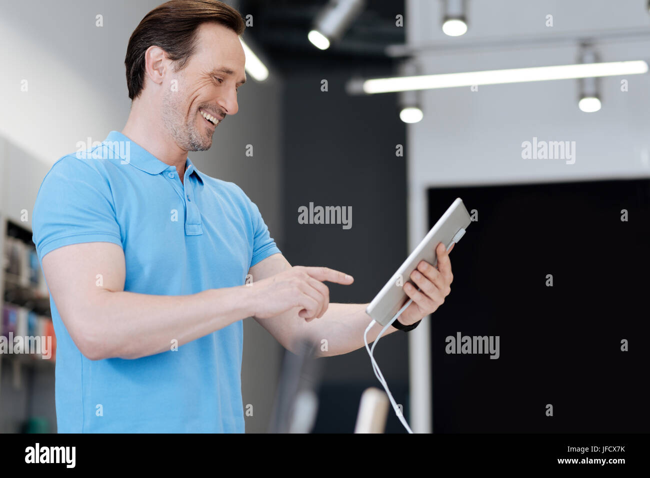 Cannot believe my eyes. Excited man cannot keep his emotions after finding a perfect gadget for a gift while shopping - Stock Image