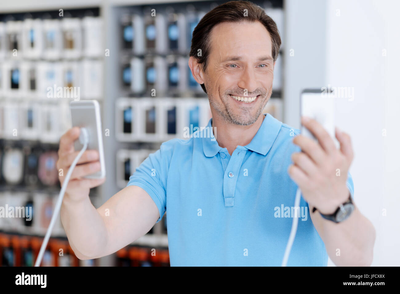 Cannot choose. Excited man holding two mockup cellphones and cannot come to a decision which one to boy while standing - Stock Image