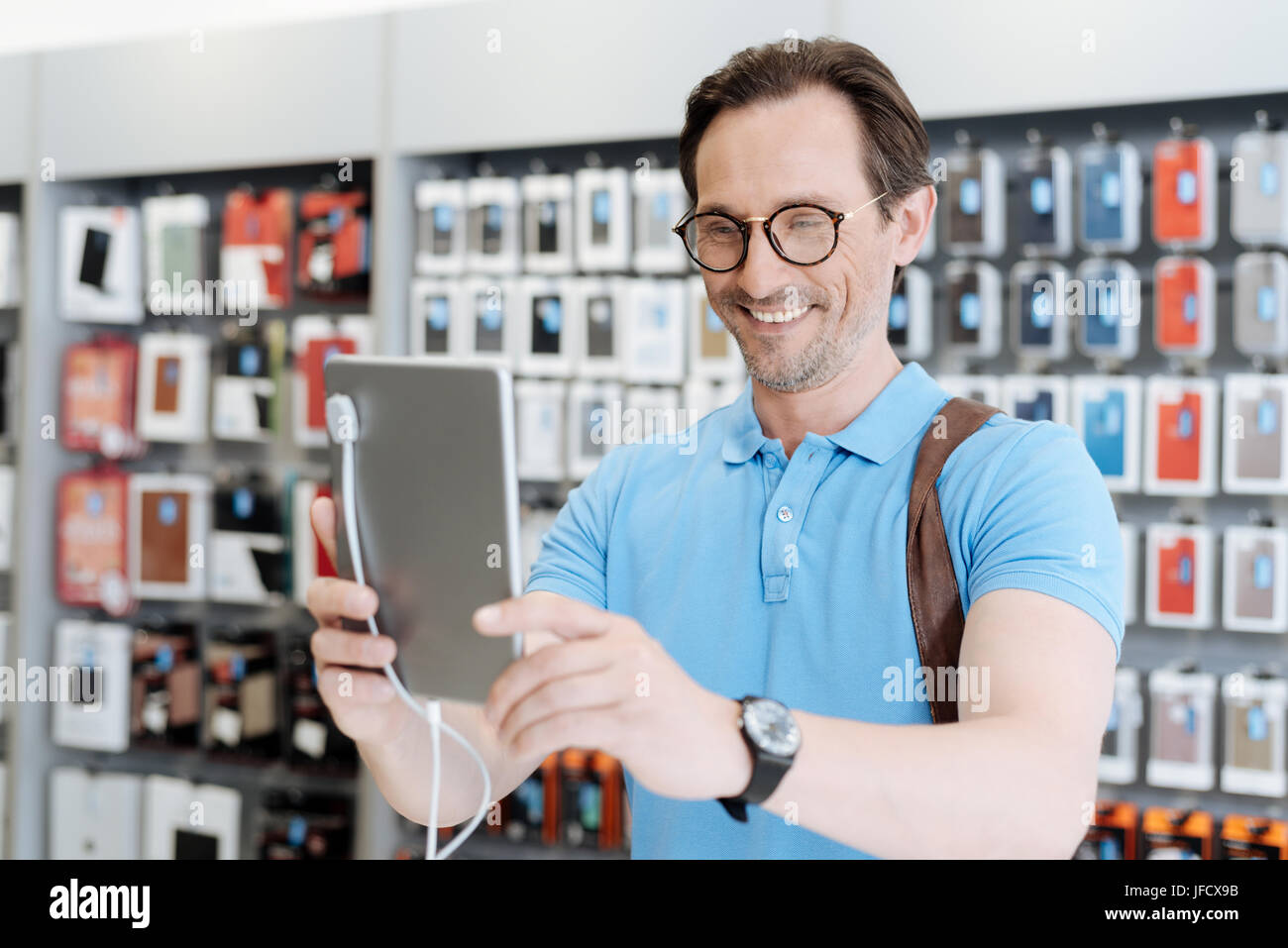 Completely satisfied with its quality. Smart man with a backpack and a black wrist watch taking selfies with a tablet - Stock Image