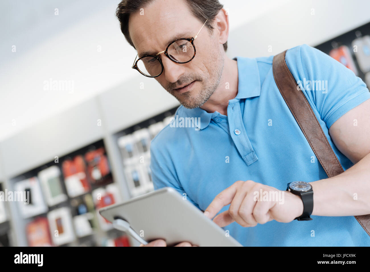 This could be a perfect gift. Male shopper focusing on a tablet and trying its technical capabilities while shopping - Stock Image
