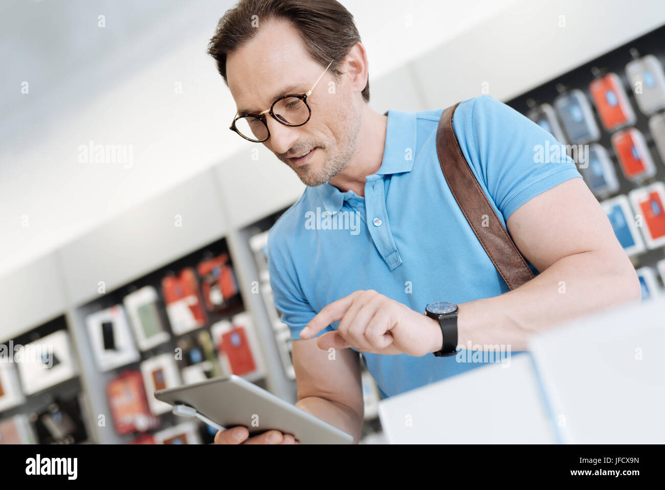 I really like this gadget. Concerned man wearing glasses standing at a display of a store and working with a mockup - Stock Image