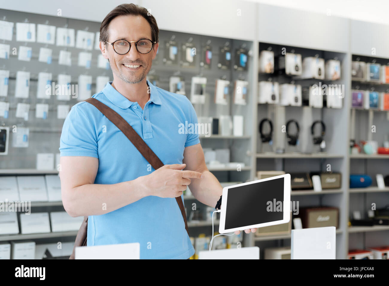 I finally found the perfect one. Busy adult man wearing glasses shopping for a new tablet and pointing his finger - Stock Image