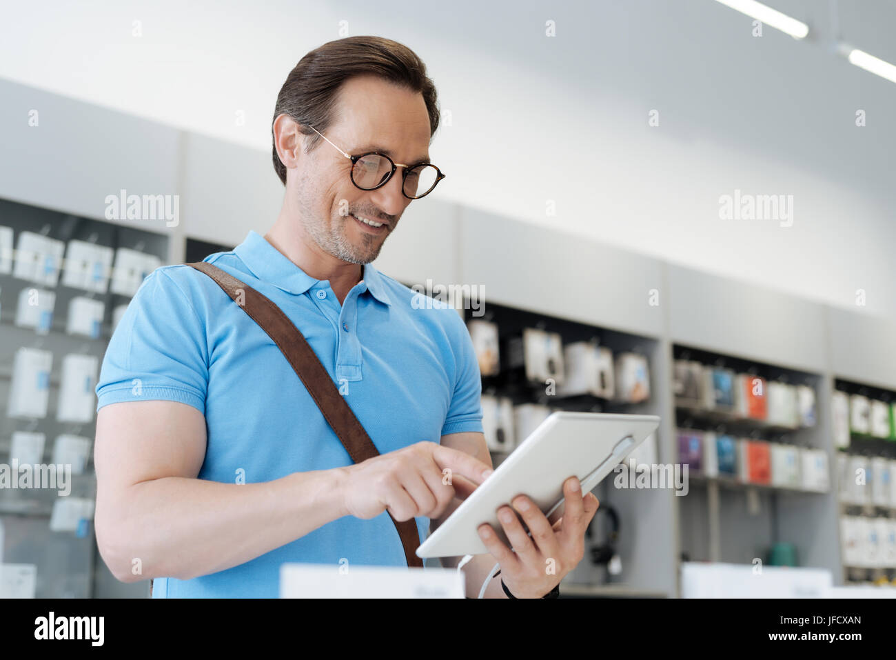 This one is real dream. Male shopper looking for a new gadget and trying out all the technological capabilities - Stock Image