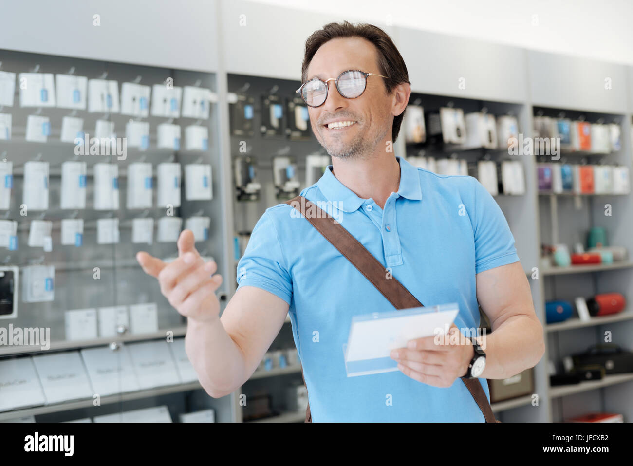 Can you help me. Emotional customer holding a product information plate and having an optic at something while shopping - Stock Image