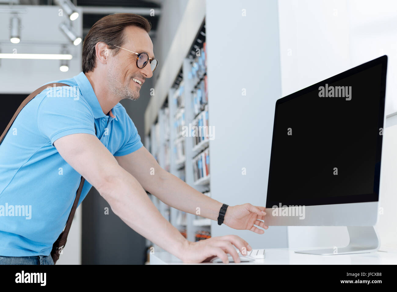 I could scarcely believe my eyes. Happy man grinning widely and leaning on a display while eying a personal computer - Stock Image