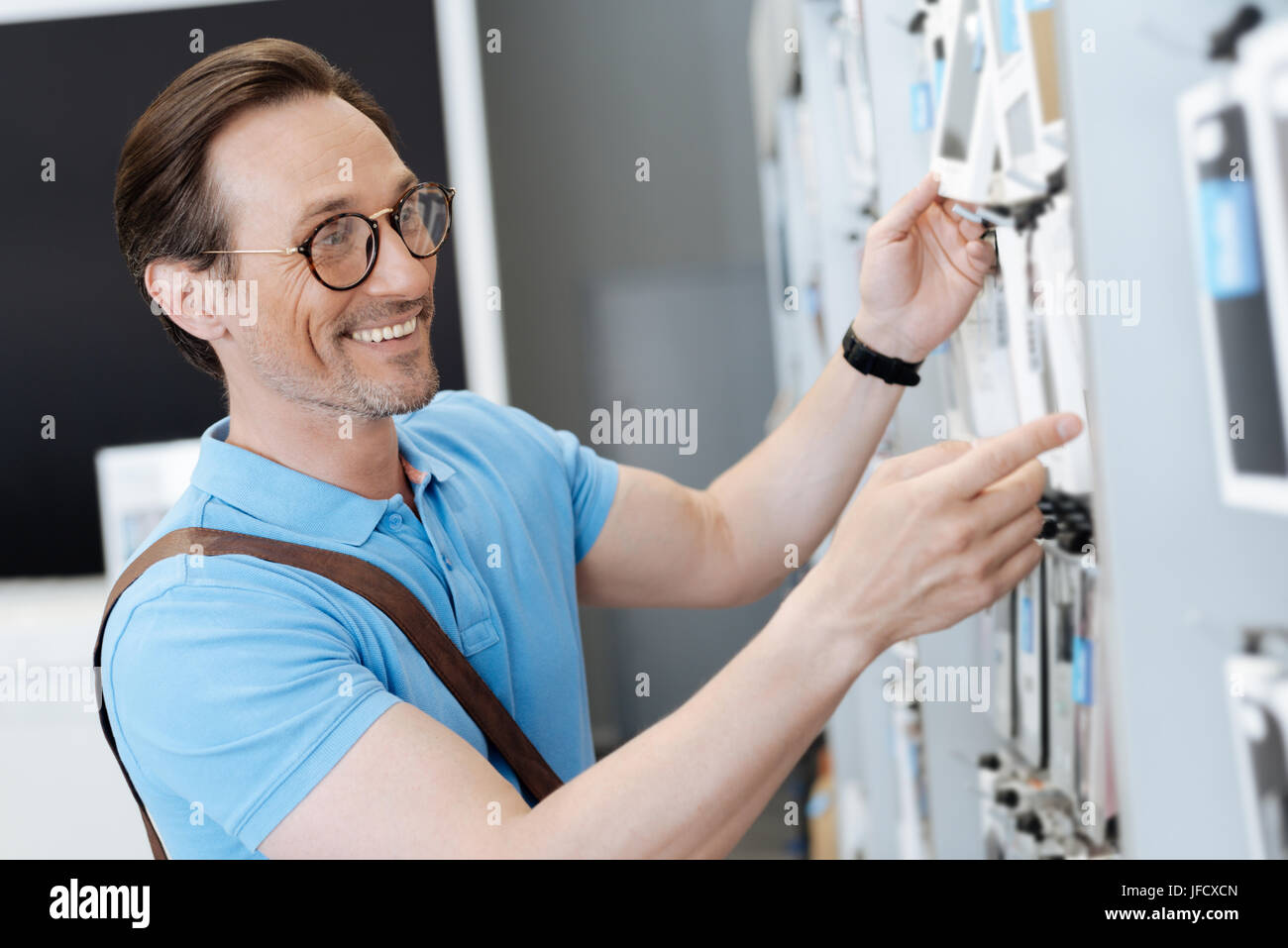 So many options. Side view on a smiling male shopper standing in the shop and looking for a phone case while shopping - Stock Image