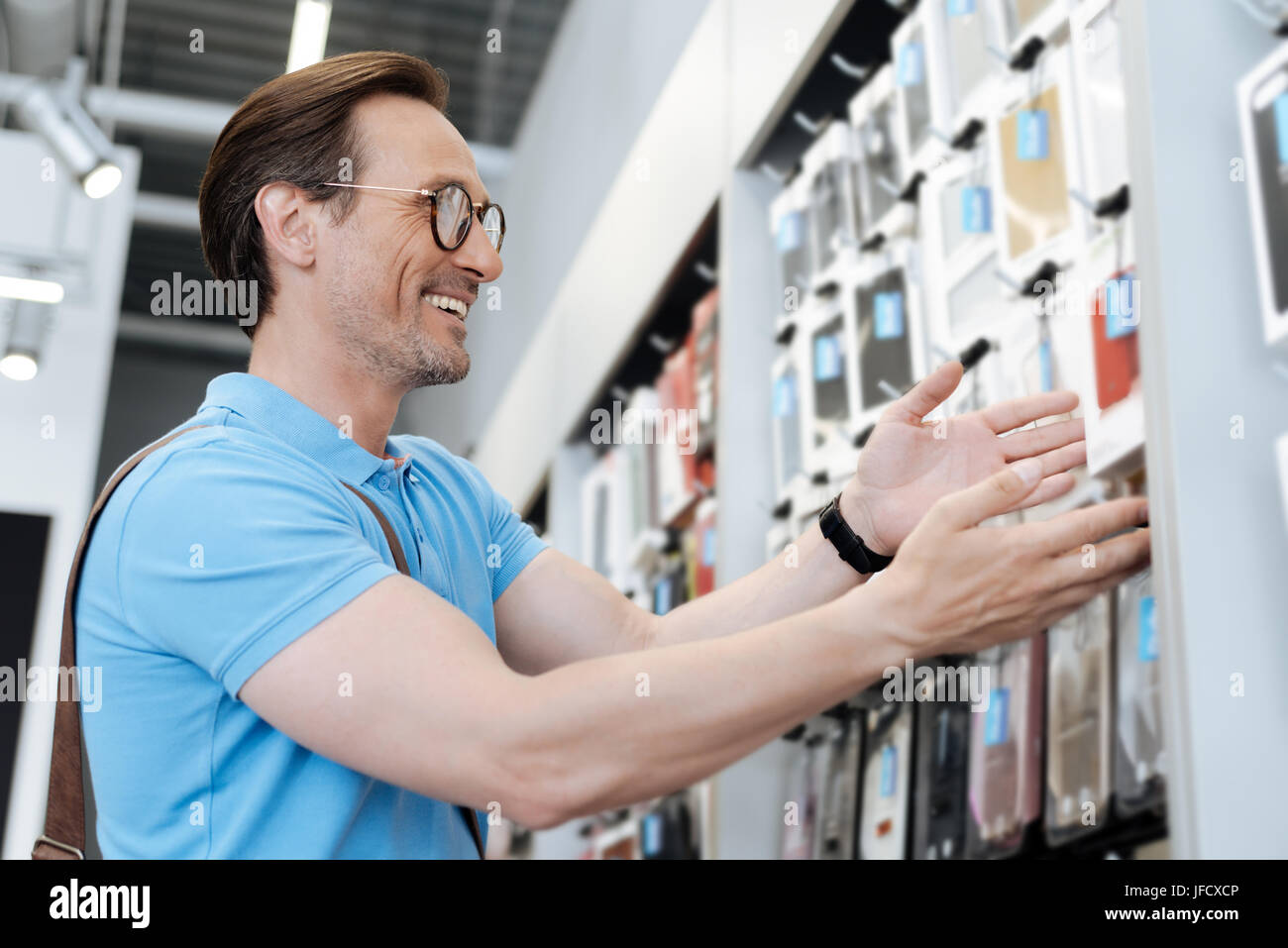 What a beautiful phone case. Positive busy man wearing glasses choosing a cover for his digital tablet or smartphone - Stock Image