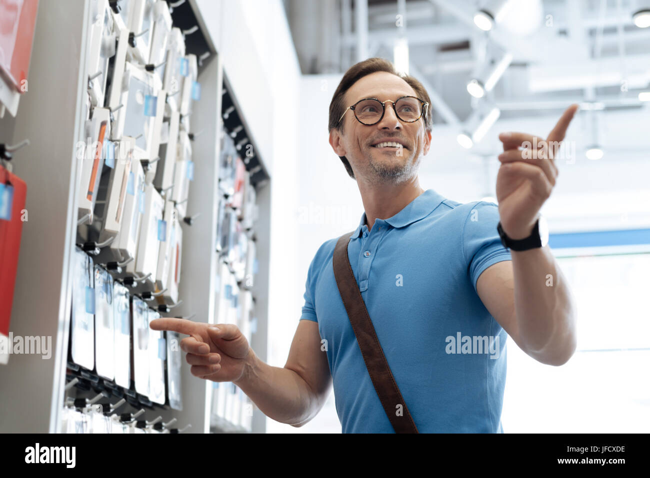Do you have it in another color. Low angle shot of a radiant man asking a salesman about the phone covers while - Stock Image