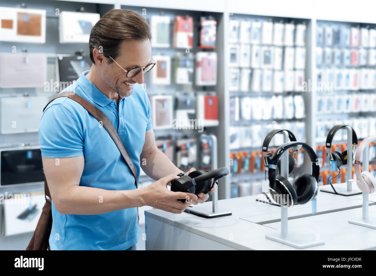 I believe these are new. Positive man wearing casual attire beaming while standing at a display and holding professional - Stock Image