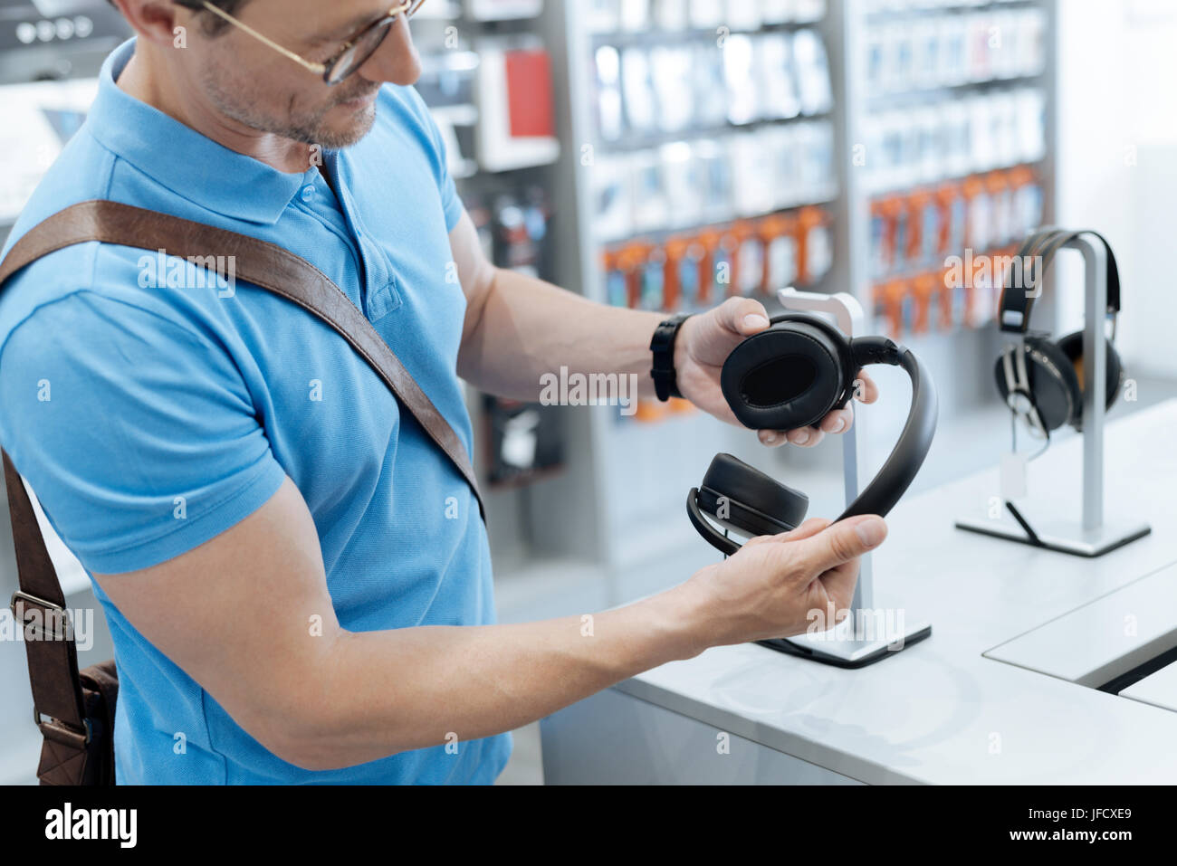 Wow they are amazing. Real music lover trying out a new pair of headphones while walking around and shopping at - Stock Image