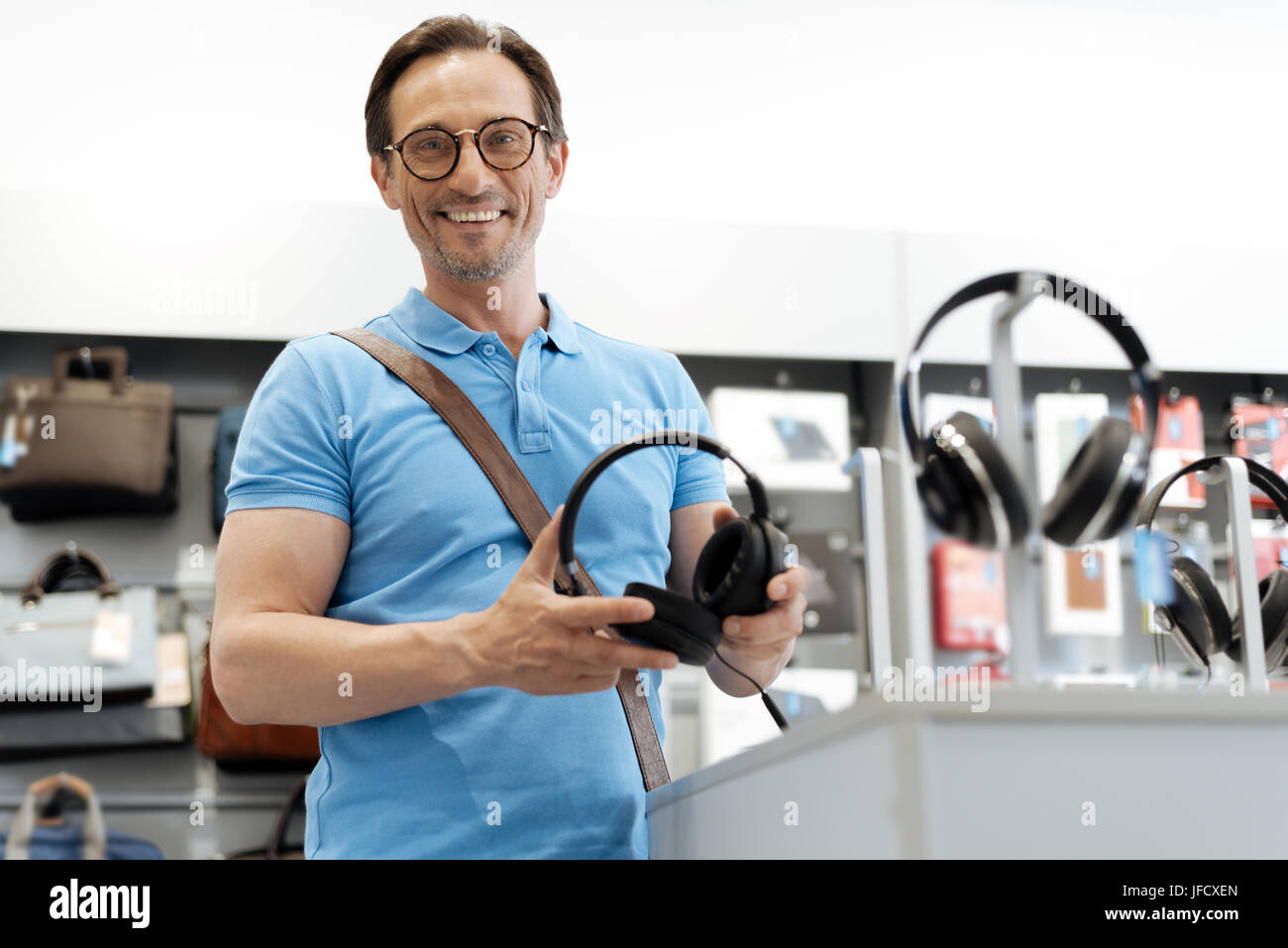 I want to buy them. Shot of a radiant male shopper holding a pair of black headphones while standing at a store - Stock Image