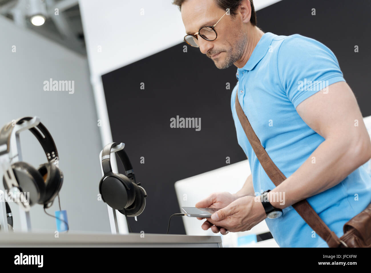 These are quite good. Focused adult customer standing at a display and trying out the latest models of headphones - Stock Image