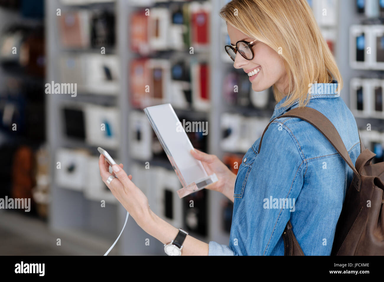 Let me take a closer look. Shot of a smiling woman with a backpack looking at a smartphone while holding a product Stock Photo