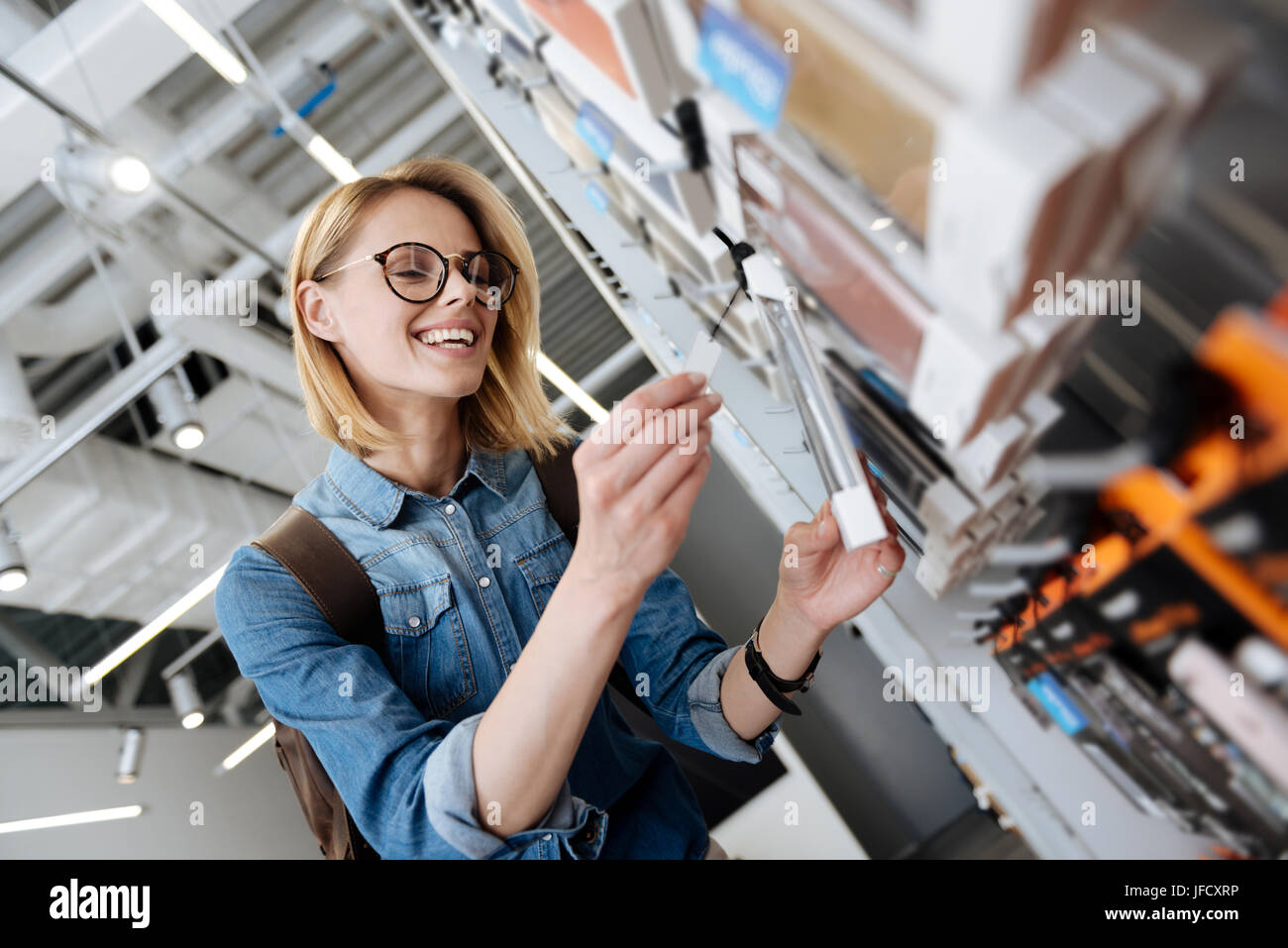 Oh I will take this one. Pretty female customer grinning widely while choosing a new cover case for her phone at - Stock Image