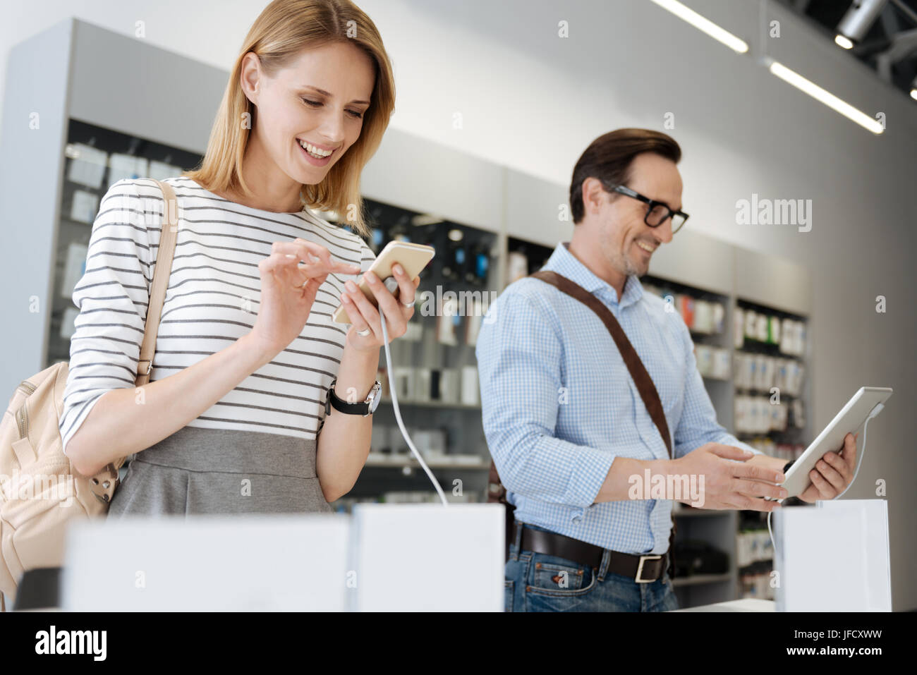 Testing in use. Excited customers checking all the technological capabilities of modern gadgets while shopping at - Stock Image