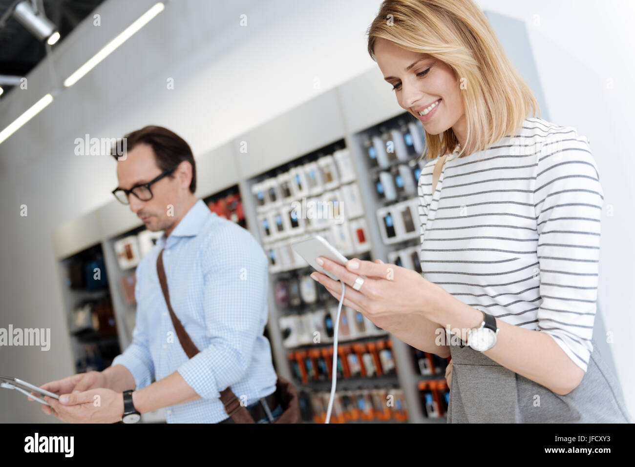 Innovative technologies are popular these days. Selective focus on a pretty blonde woman smiling while testing the - Stock Image
