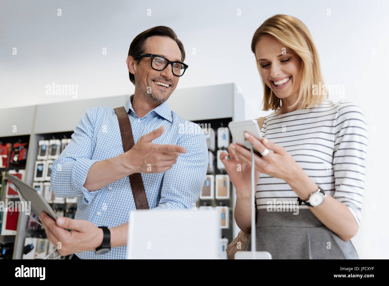 Do you like this one. Excited man and woman beaming while discussing technological capabilities of mockup technological - Stock Image