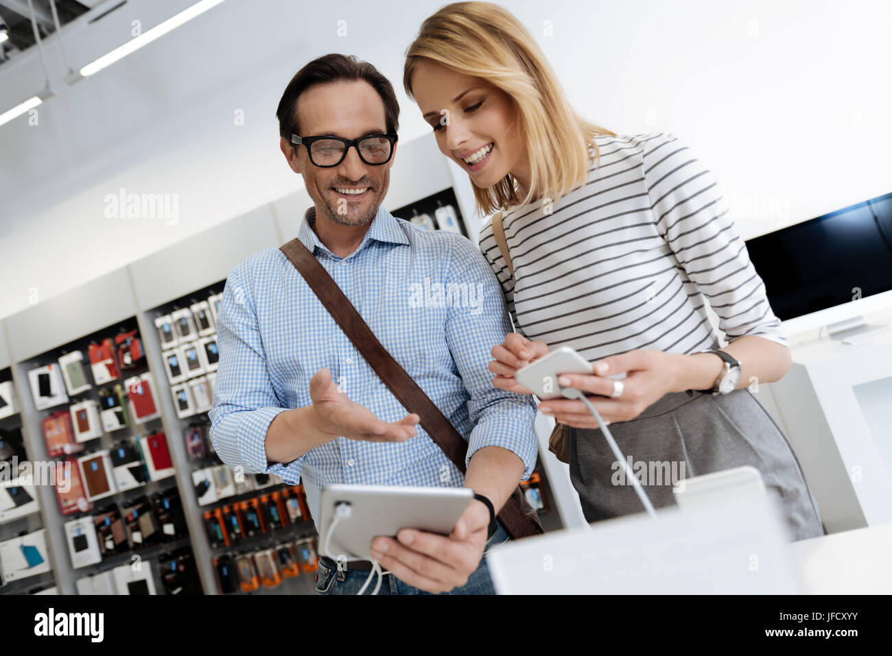 Check this out. Smiling man and woman wearing casual attire standing at a store display and trying out technological - Stock Image