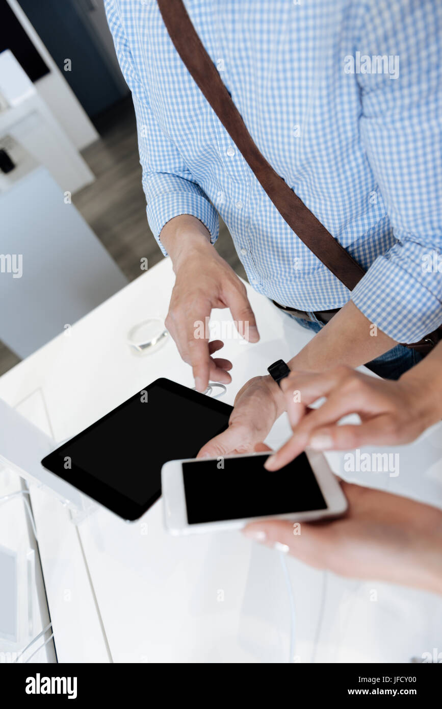 It is better than a previous model. Close up look on customers using different gadgets while standing at a display - Stock Image