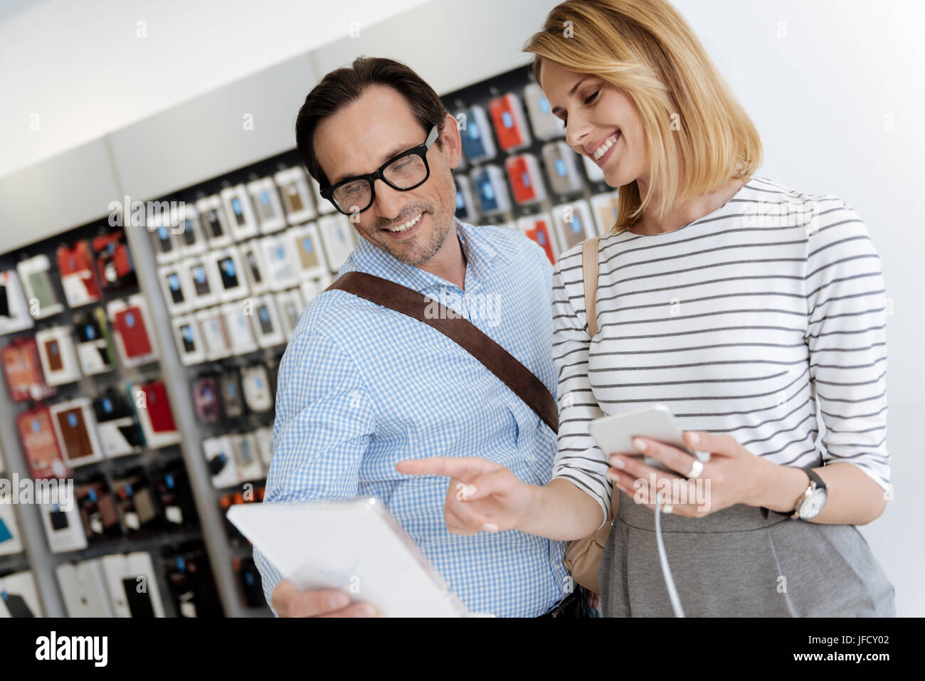 Oh I like this one. Full of life couple having a chat while looking at a tablet computer and shopping at an electronics - Stock Image