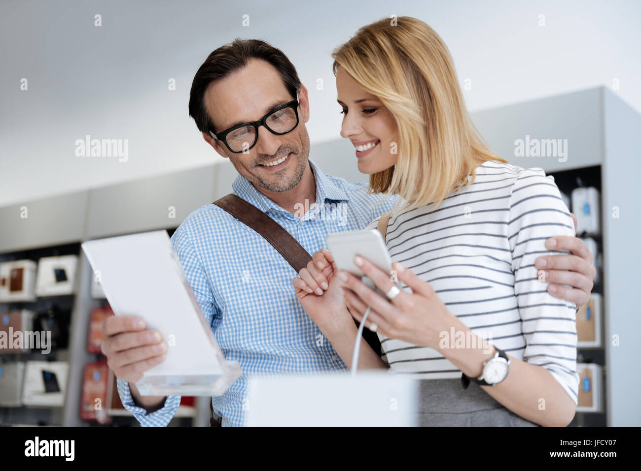 Let me look at the characteristics. Charming radiant couple holding and looking at cellphone information plate while Stock Photo