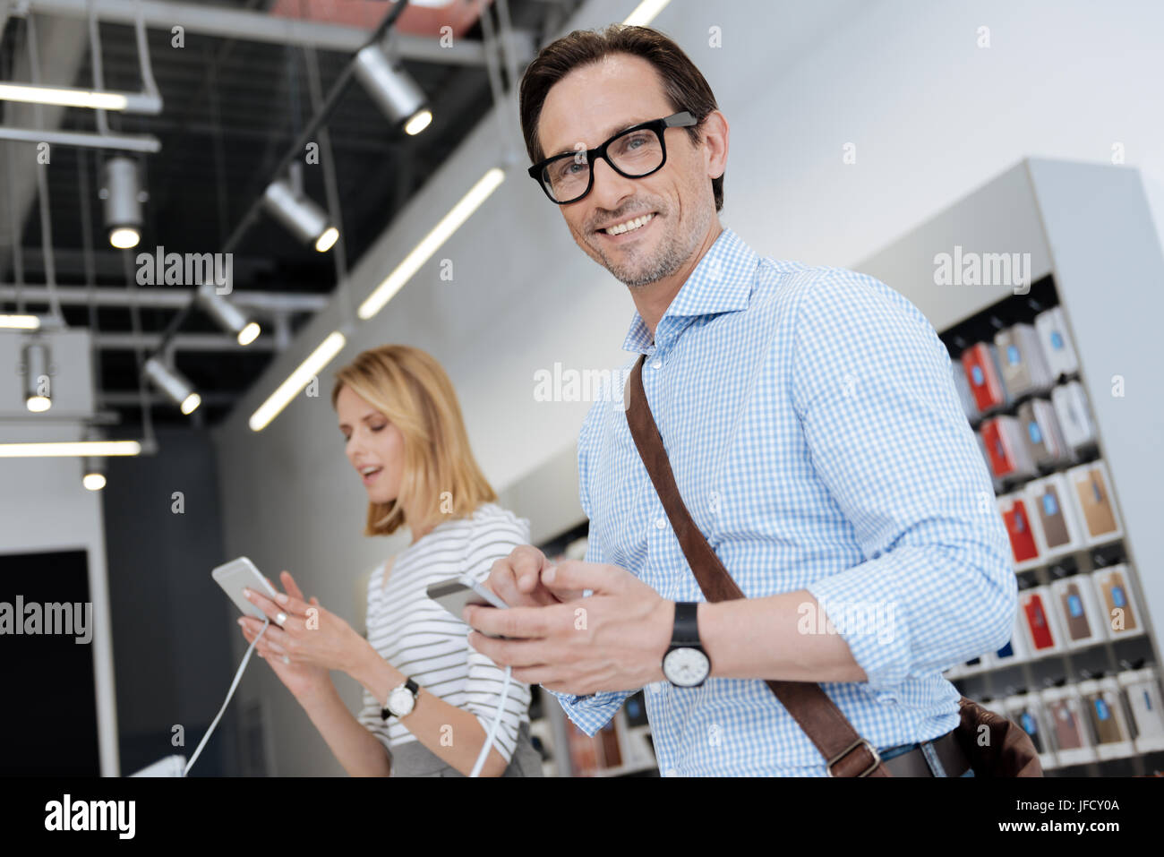 Cannot believe my eyes. Selective focus on a friendly man standing holding a phone and grinning widely while a female - Stock Image