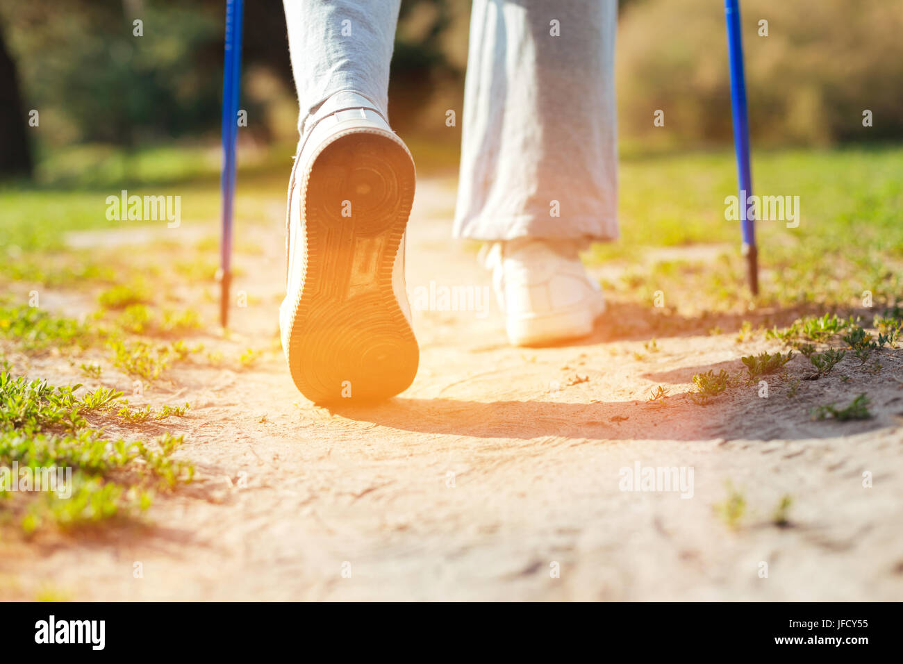 Movement is life. Close up of a person holding Nordic walking poles and going forward while being in the park - Stock Image