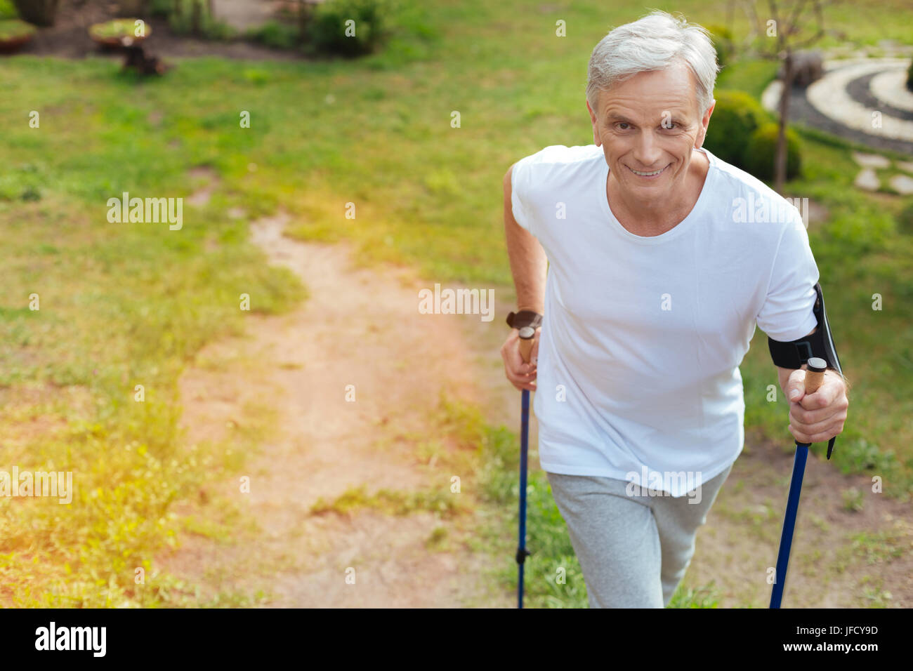 Pleasant workout. Positive delighted aged man smiling and going forward while enjoying his workout - Stock Image
