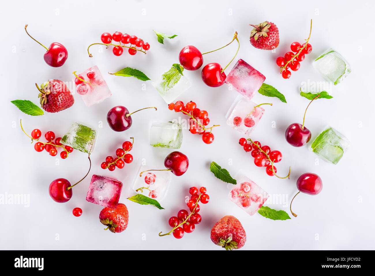 Top view ice cubes with fresh berries among not frozen cherry, strawberry and mint leafs on the white background. - Stock Image