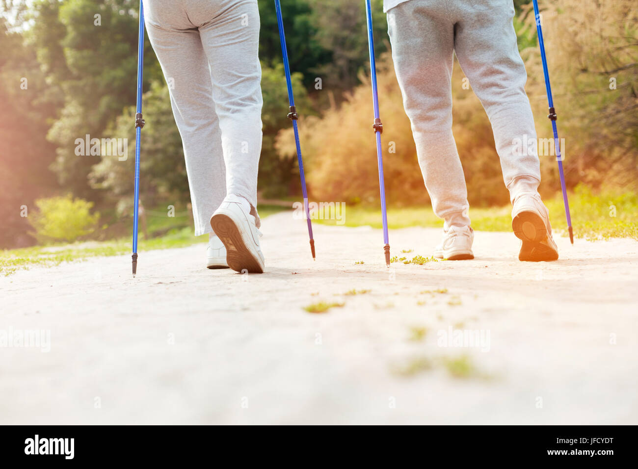 In synch. Sporty nice elderly couple holding Nordic walking poles and going forward while exercising together - Stock Image