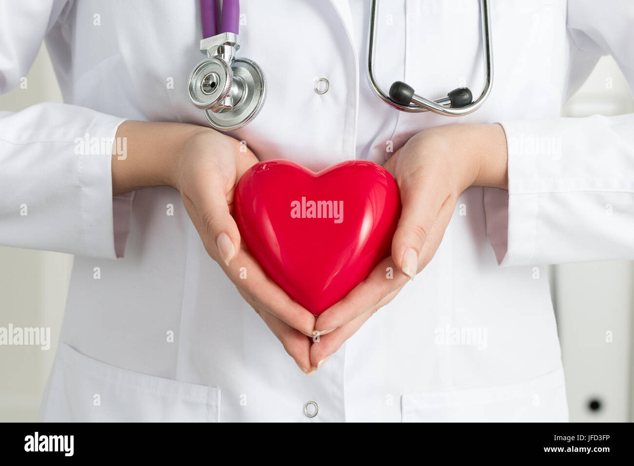 Female doctor's hands holding red heart. Doctor's hands closeup. Medical help, prophylaxis or insurance - Stock Image