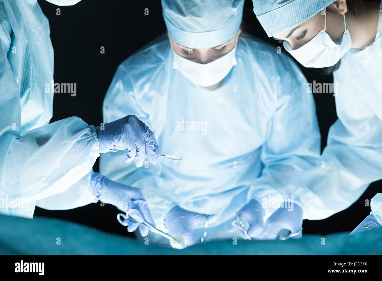 Medical team performing operation. Group of surgeon at work in operating theatre toned in blue - Stock Image