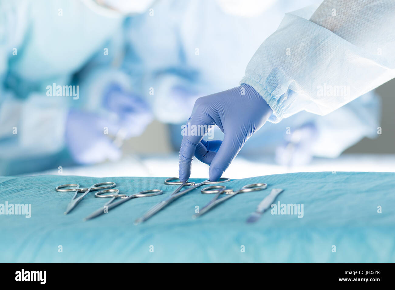 Close-up of scrub nurse taking medical instruments for operation with colleagues performing in background - Stock Image