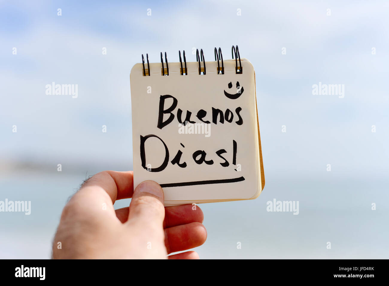 closeup of a young caucasian man outdoors showing a spiral notepad with the text buenos dias, good morning in Spanish - Stock Image