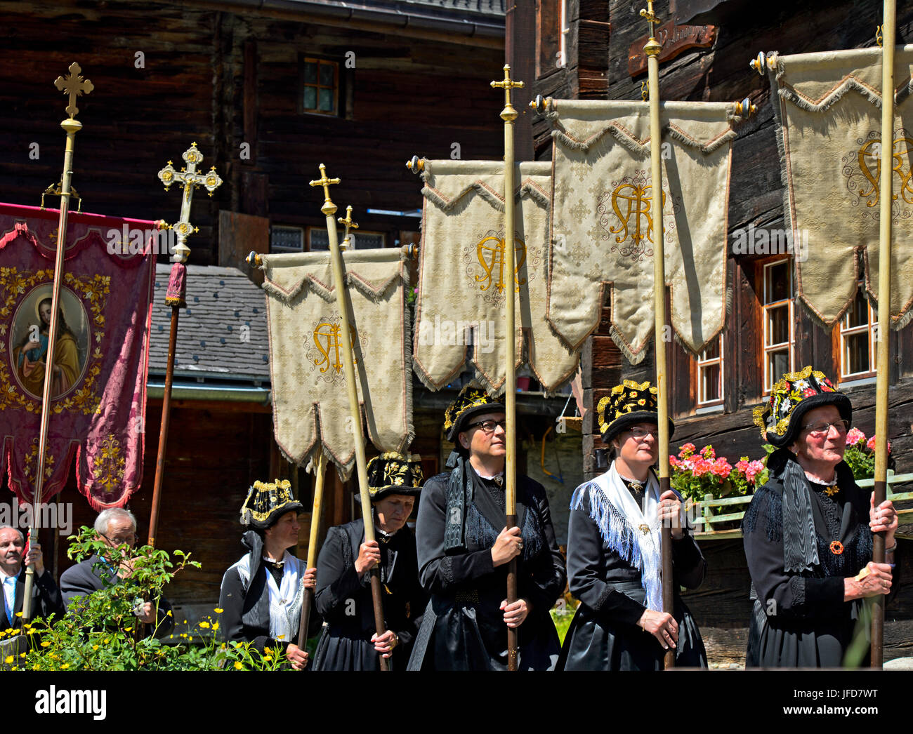 Woman in traditional costumes with church banners, flags, Corpus Christi procession, Blatten, Lötschental, - Stock Image