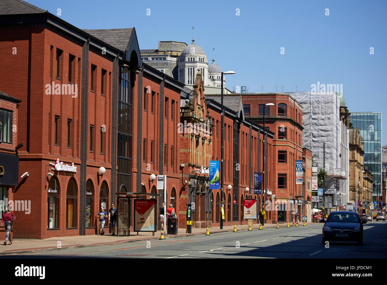 Looking down Deansgate 298 in Manchester city centre,  Santander Corporate Banking buildings. and parking bays suspended. - Stock Image