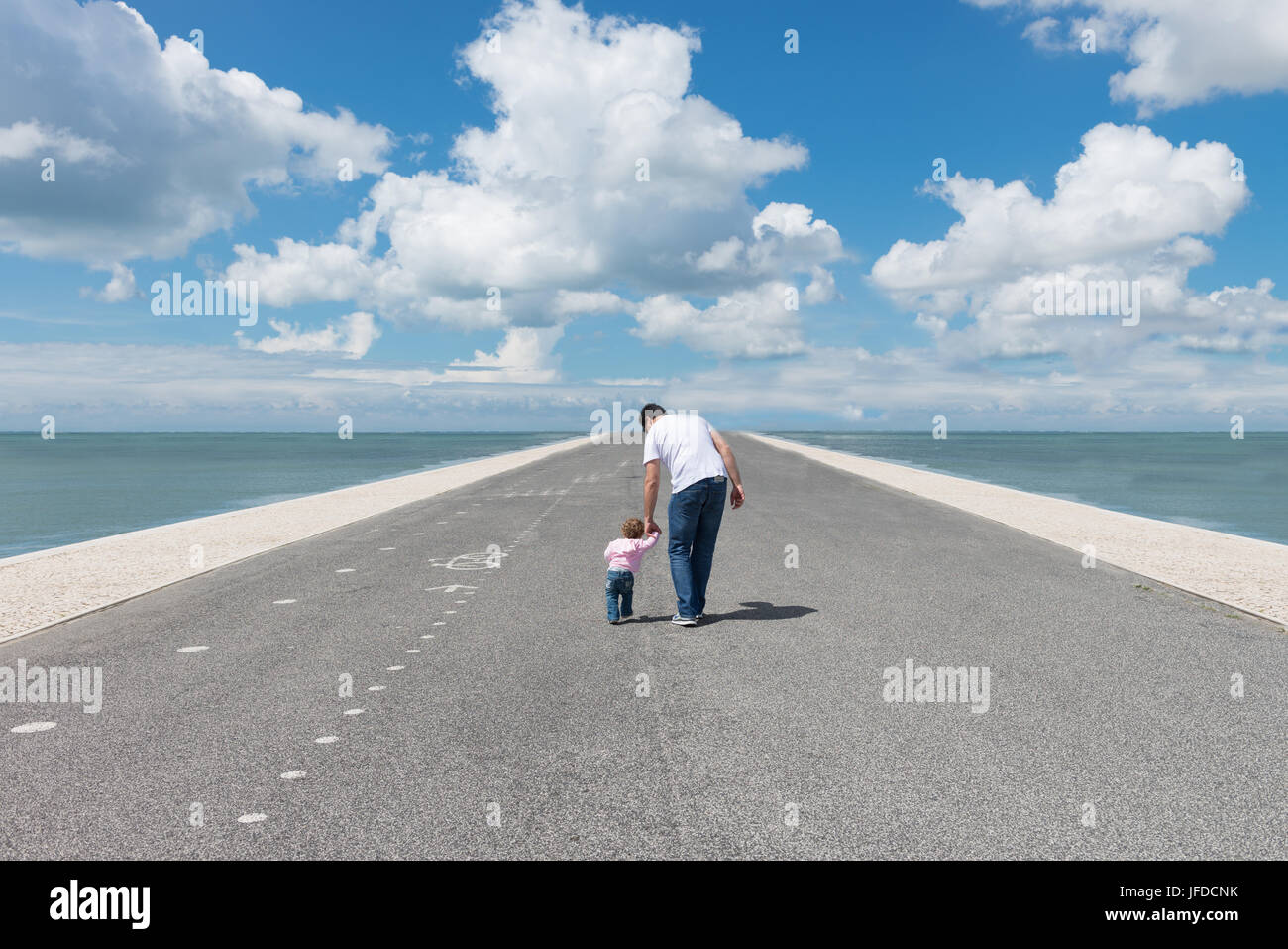 Careful father guiding his baby girl on - Stock Image