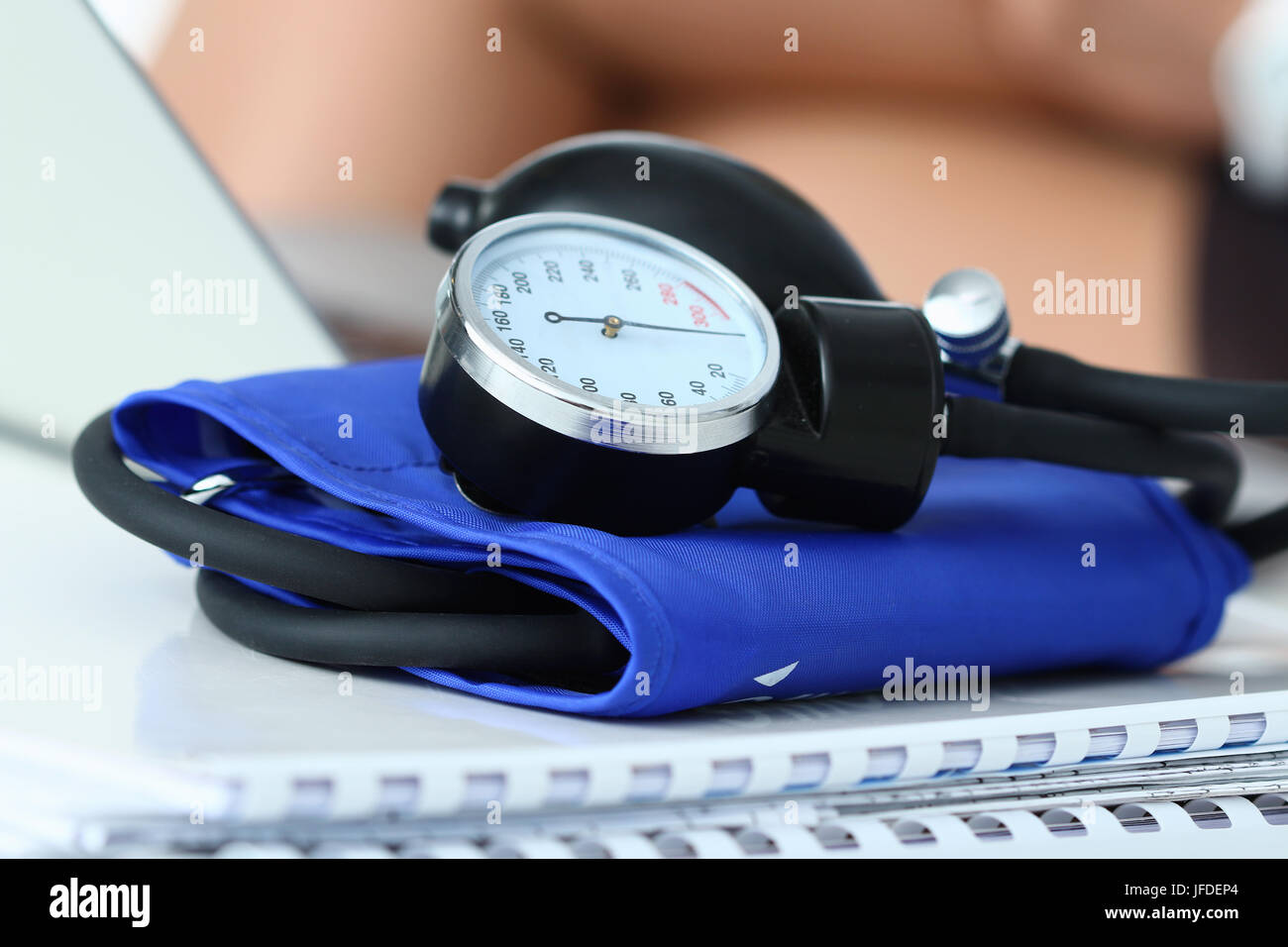 Medicine doctor working place. Close up view of manometer laying on working table at physician office. Hospital - Stock Image