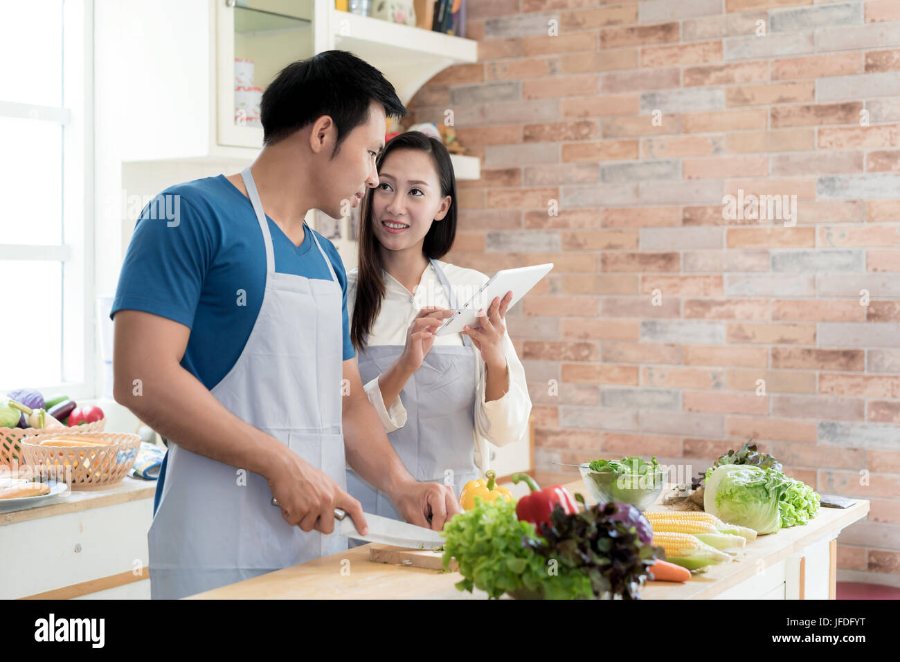 Asian beautiful young husband and wife searching menu recipe in digital tablet in kitchen at home. Happy love couple - Stock Image