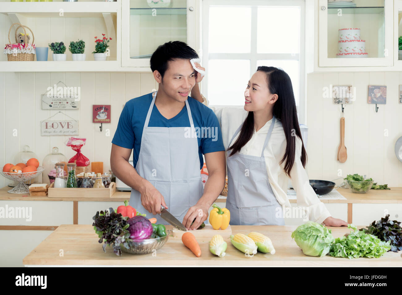 Asian beautiful young wife helping husband dry sweat off his face in kitchen at home. Happy love couple concept. Stock Photo