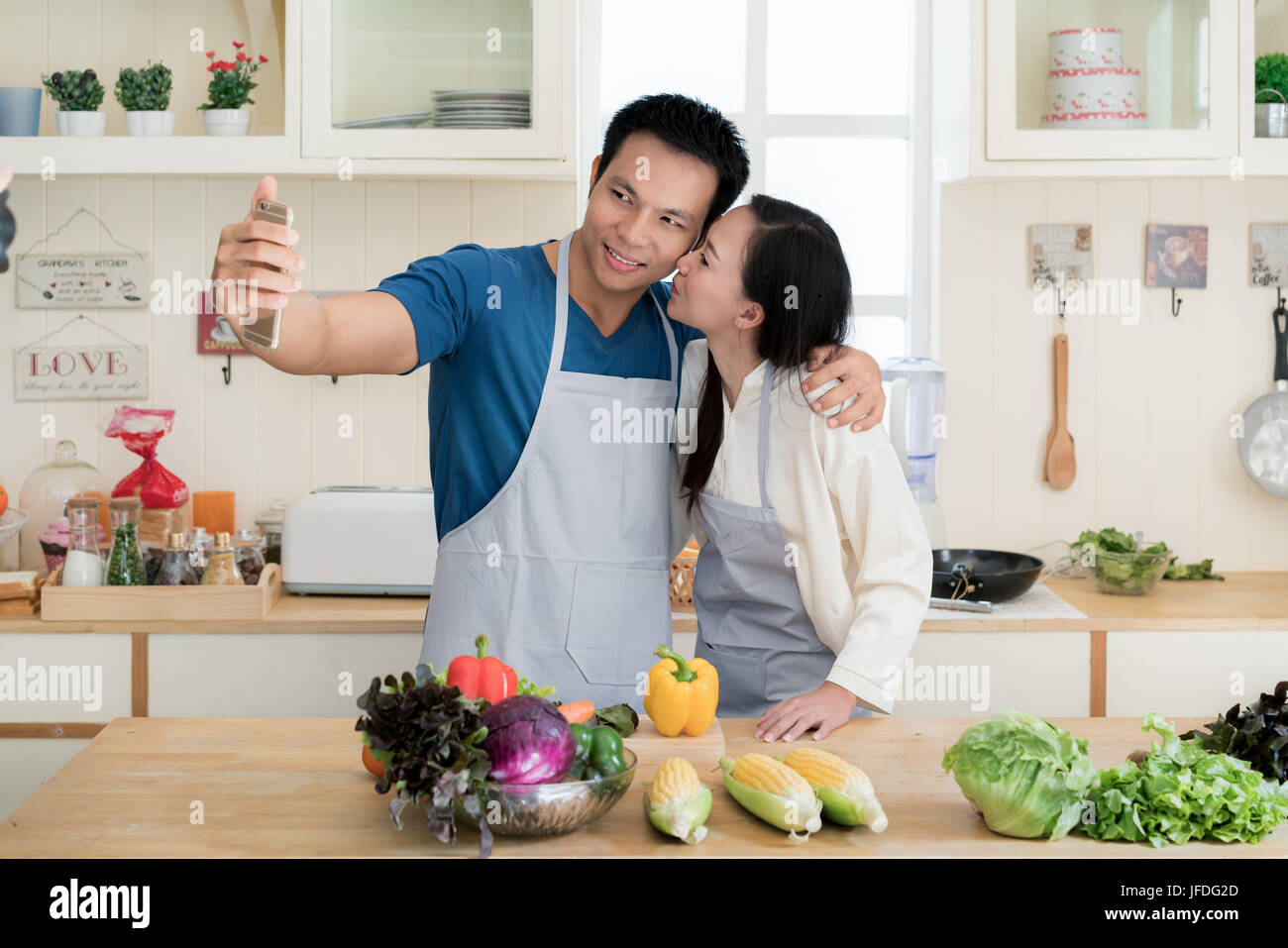 Asian handsome guy is smiling and cooking in kitchen while doing selfie using smartphone at home. Happy love couple - Stock Image