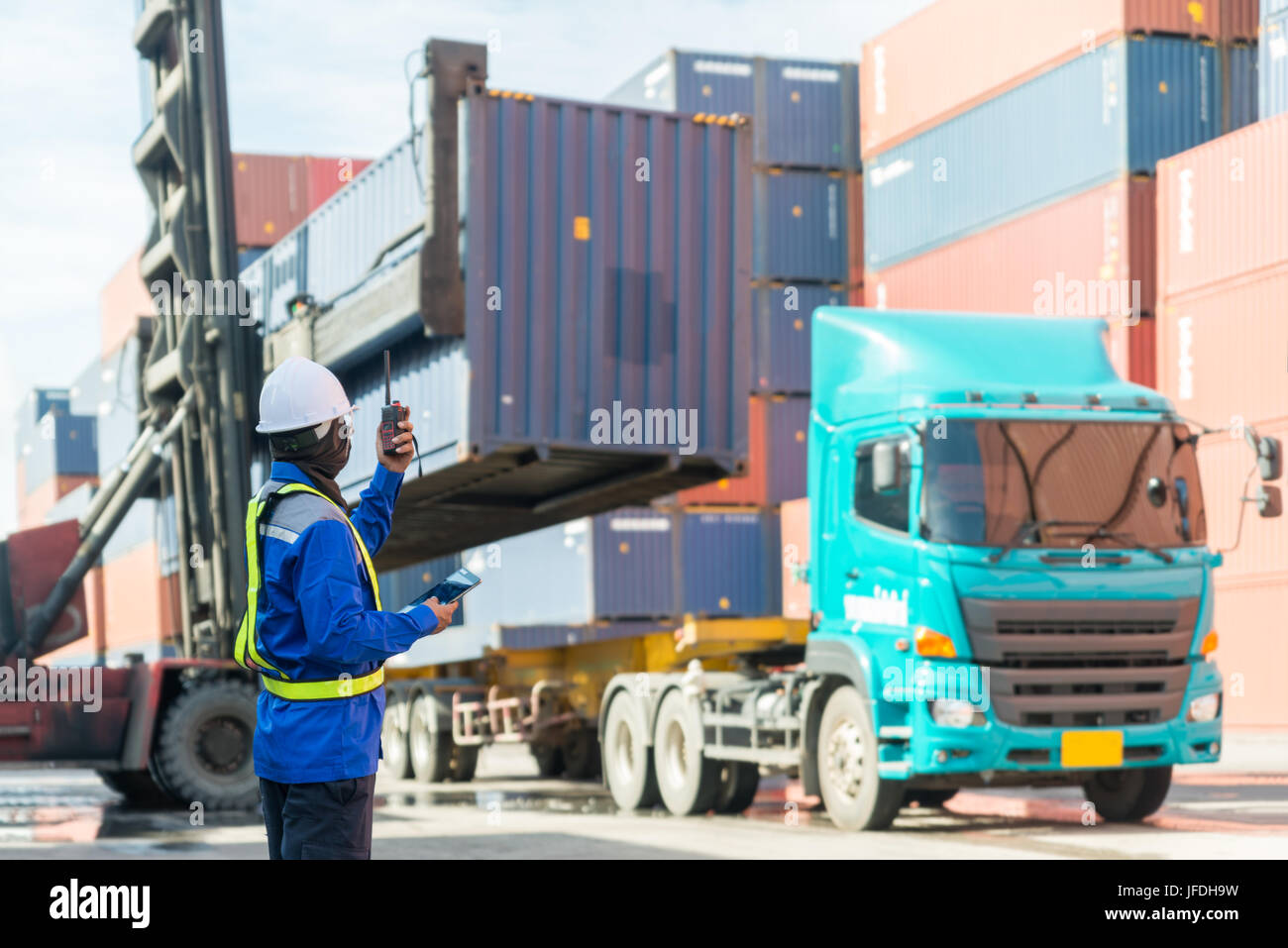 Foreman control loading Containers box from Cargo freight ship for logistics import export background. - Stock Image
