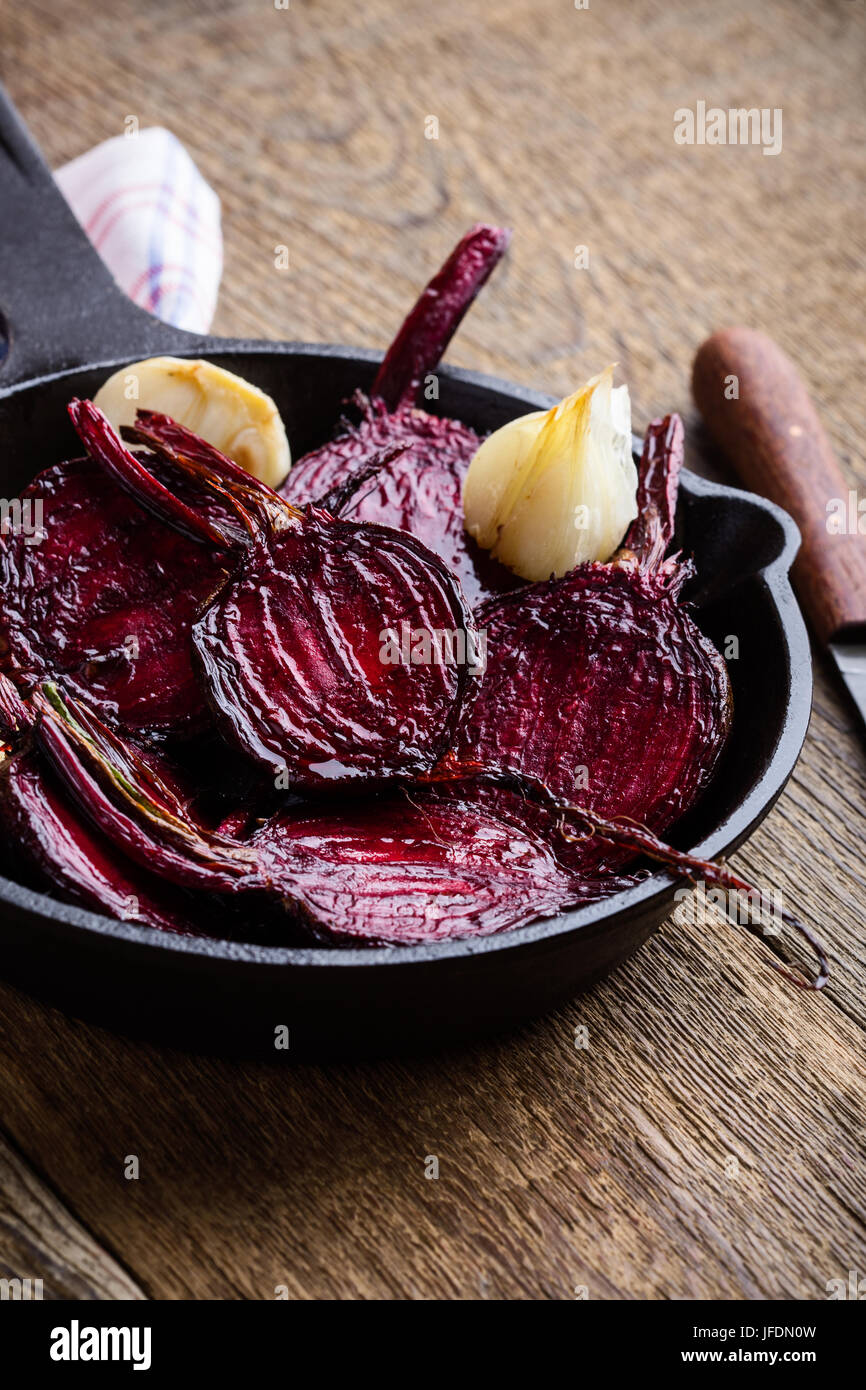 Roasted beetroots in cast iron skillet on wooden rustic table - Stock Image