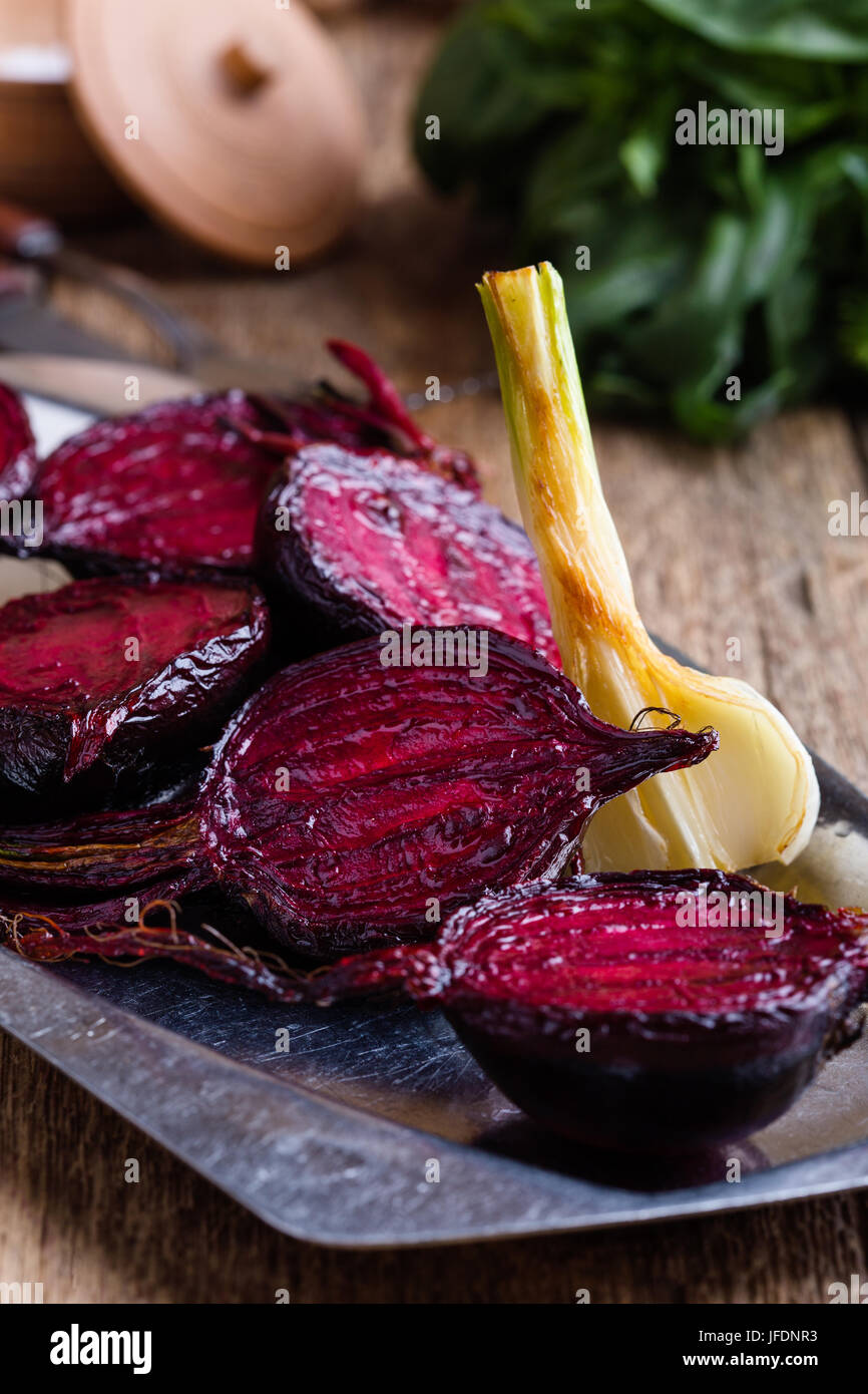 Sliced baked beetroot on rustic outdoor party table, diet and  healthy eating food concept - Stock Image
