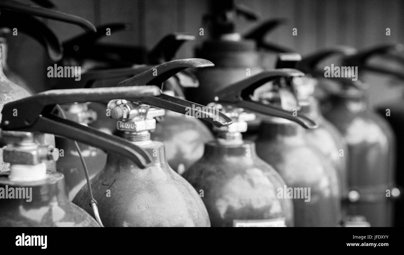 Black and white image of fire extinguishers ready to be used at a fire drill. - Stock Image