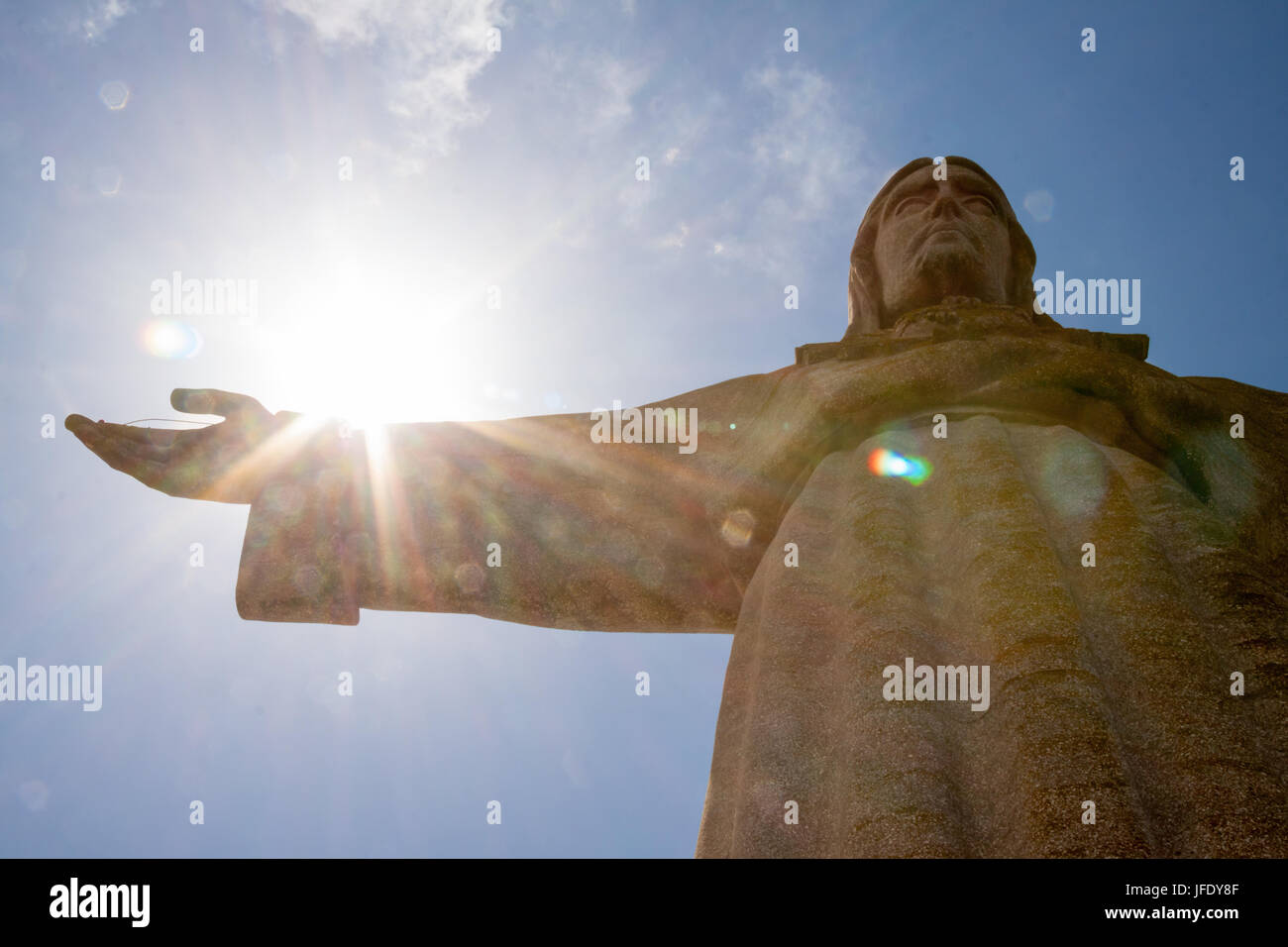 Sun behind Christus Rei Statue  in Lisbon, Portugal, Europe - Stock Image