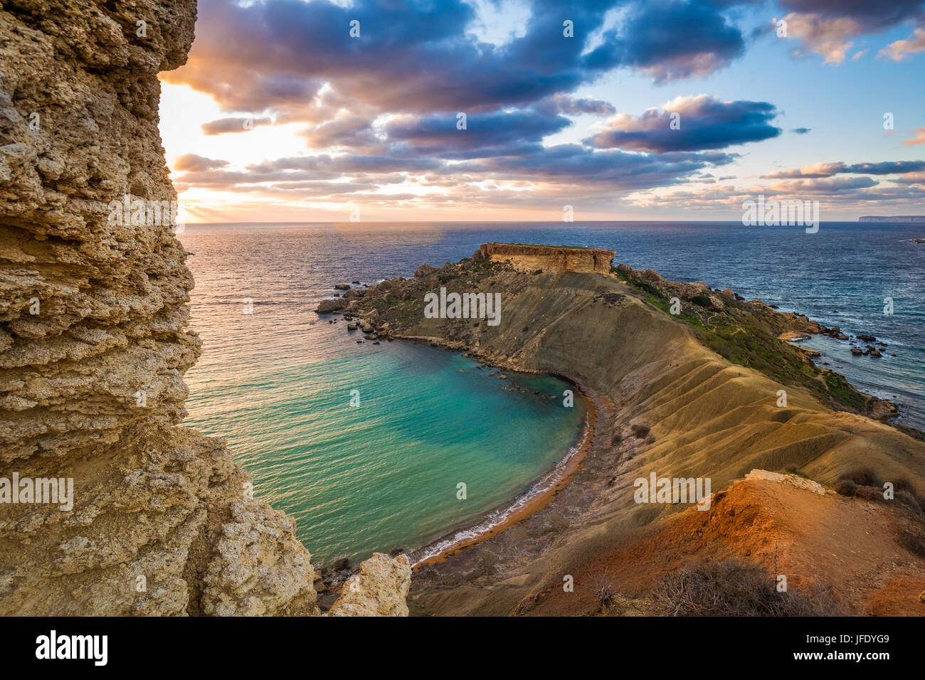 Mgarr, Malta - Panorama of Gnejna bay, the most beautiful beach in Malta at sunset with beautiful colorful sky and - Stock Image
