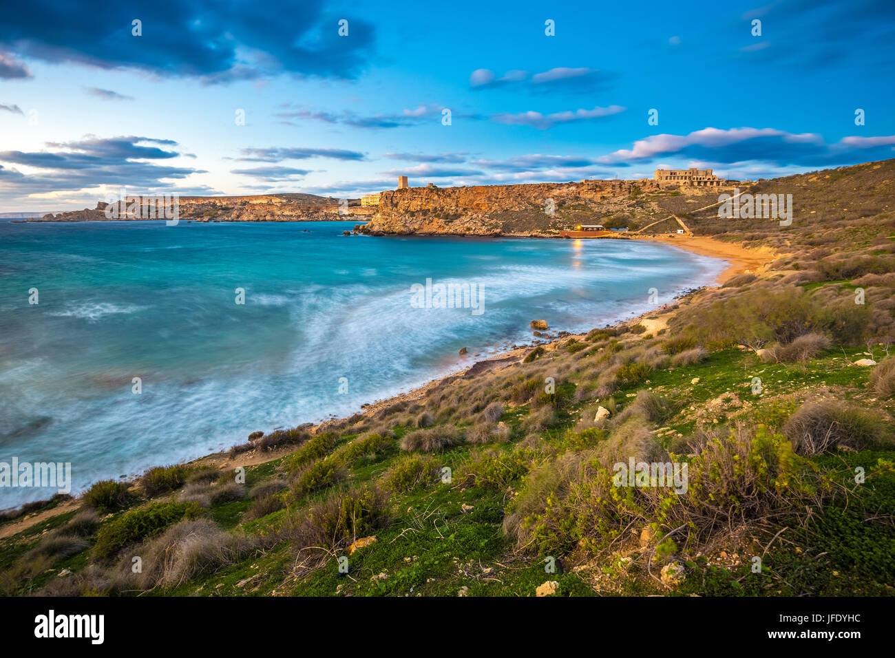 Mgarr, Malta - The famous Ghajn Tuffieha bay at blue hour on a long exposure shot with beautiful sky and clouds - Stock Image