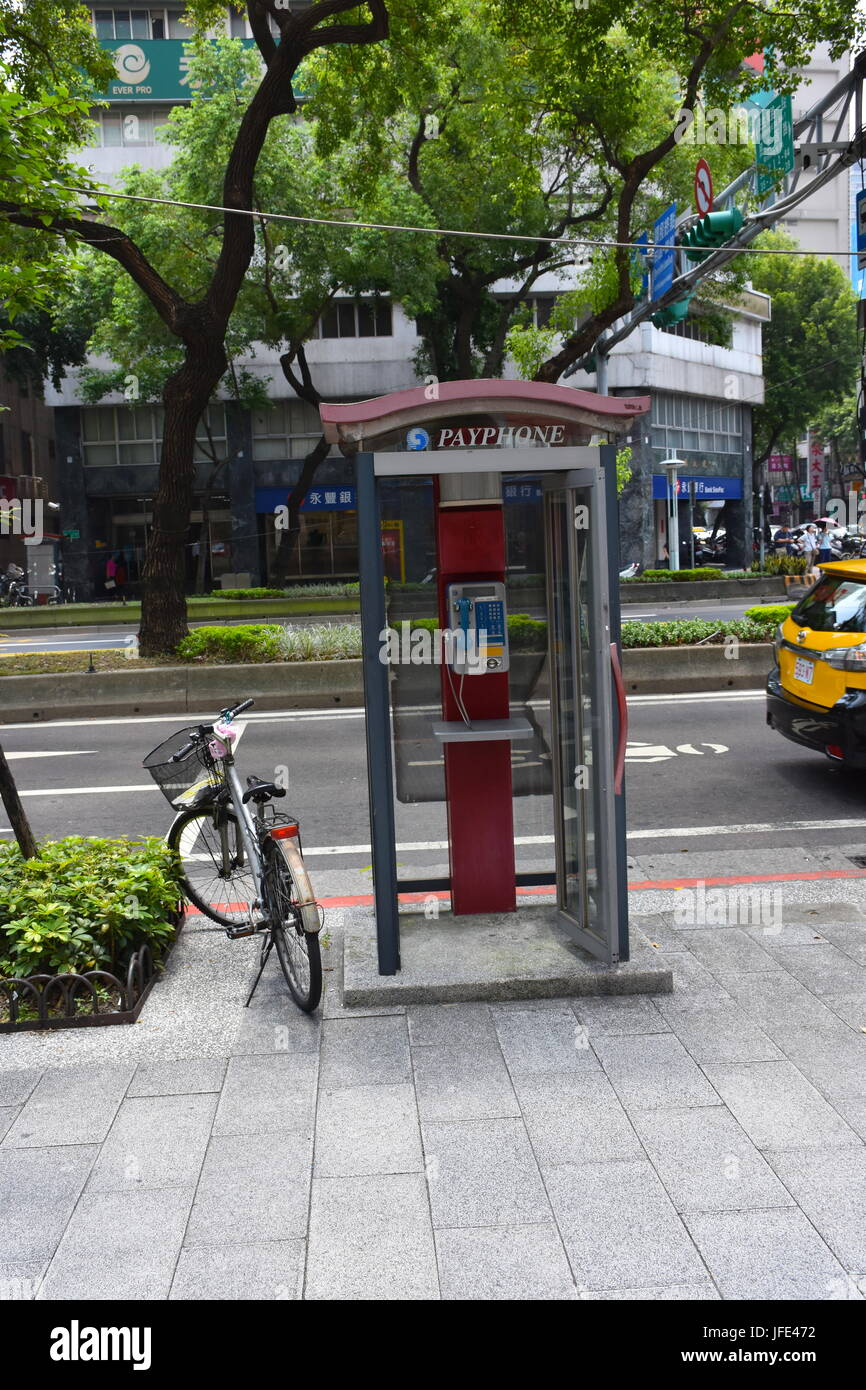A bicycle parked next to a public phone booth on the curb in Taipei, Taiwan along the street. - Stock Image
